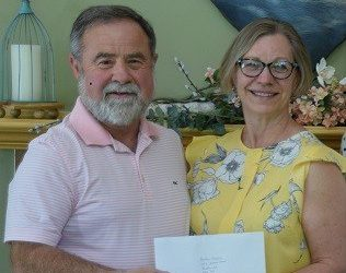 Pictured is Gerald Tracey, Hospice Renfrew Board Chair, receiving a donation from Susan Dupuis